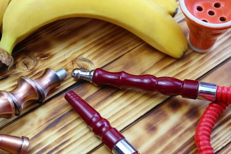 red hookah pipe lies next to a banana on a wooden Stock Photo