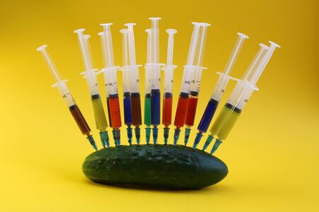 fresh cucumber studded with a multi-colored syringe