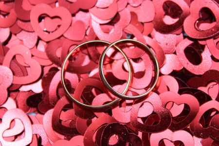 wedding rings on the background of small hearts