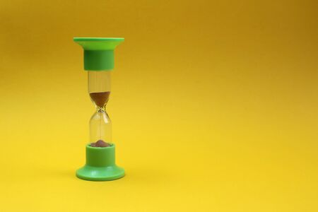 hourglass stand on a yellow background