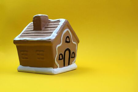 toy house piggy bank stands on a yellow background