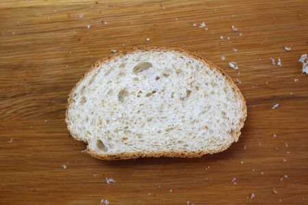 One piece of bread with crumbs lies on a cutting board Banco de Imagens