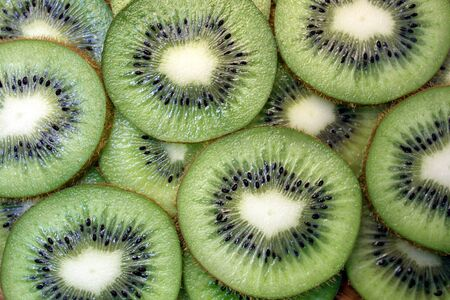 Kiwi sliced in circles lies on a flat surface texture Reklamní fotografie