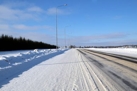 Winter road on a sunny day with snowdrifts along the edges