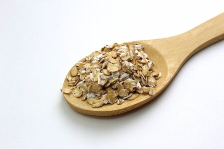 Oat groats on a wooden spoon on a white background