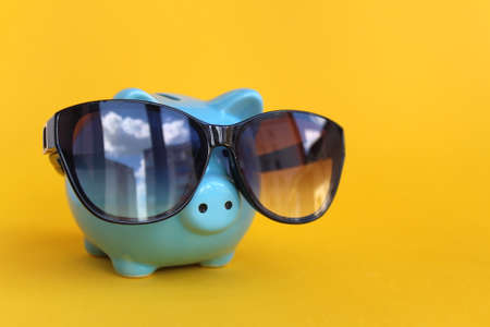 Piggy piggy bank with sunglasses on a yellow background