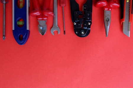 Small repair tools on a red background