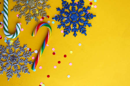 Texture of snowflakes and candy cane lie on a yellow background Archivio Fotografico