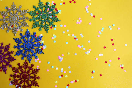 Christmas mood, snowflakes with confetti on a yellow background Archivio Fotografico