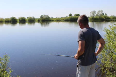 A fisherman stands with a fishing rod and looks at the water