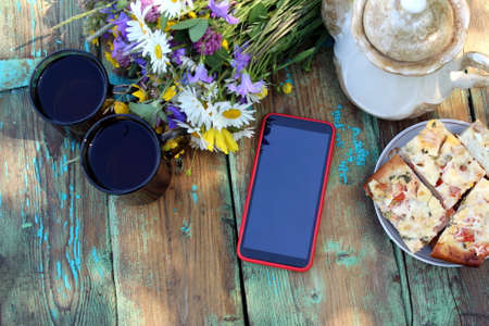 Phone on the table with a bouquet of flowers Фото со стока
