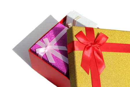 Three gift boxes of different colors stand on a white background