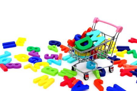 Multicolored plastic letters on a white background lie in a mini shopping cart