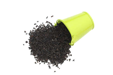 Loose black tea in a decorative bucket on a white background Stock Photo