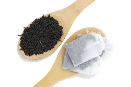 On wooden spoons lies tea in a bag and loose leaf Stock Photo