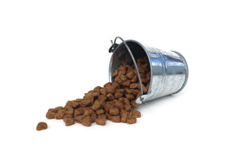 Cat food falls out of the bucket on a white background