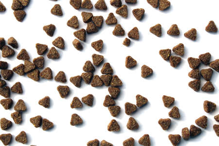 Brown cat food scattered on a white surface Stock Photo