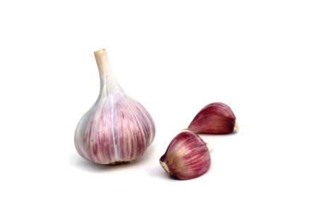 Garlic stands on a white background and small cloves nearby