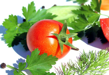 One tomato lies on a white background of green parsley and dill leaves