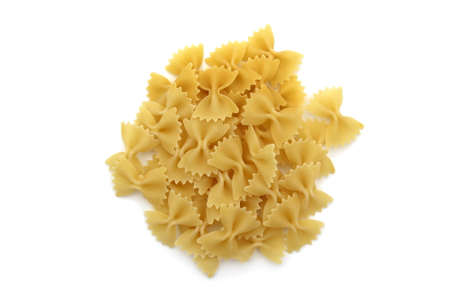 Pasta in the form of a bow lie in one heap on a white background
