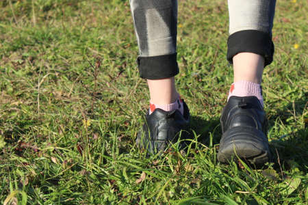The legs of a girl walking on the grass are visible