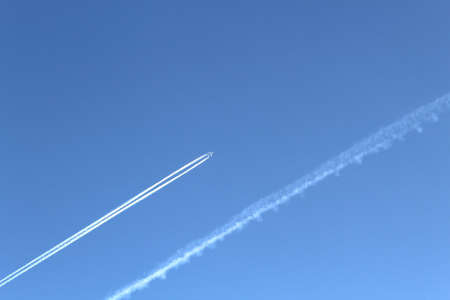 The plane flies high above the ground leaving a white trail. blue blue bright sky without clouds Stock fotó