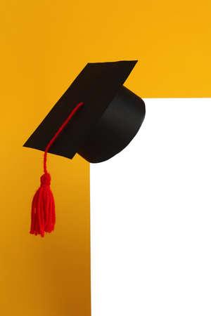 Graduation black cap lies on a white sheet of paper Reklamní fotografie