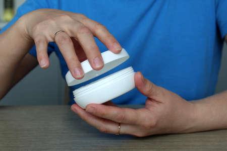Woman`s hand opens a jar of face cream Reklamní fotografie