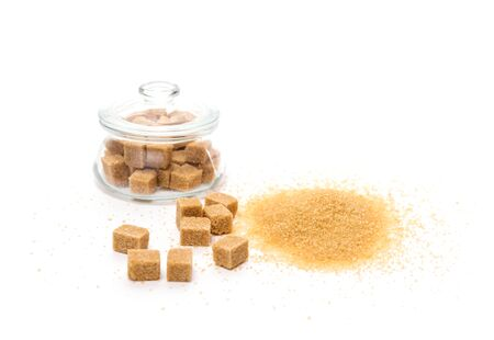 Sugar crystals and sugar cubes on a white table. Sugar cubes in a clear jar. Isolated background.