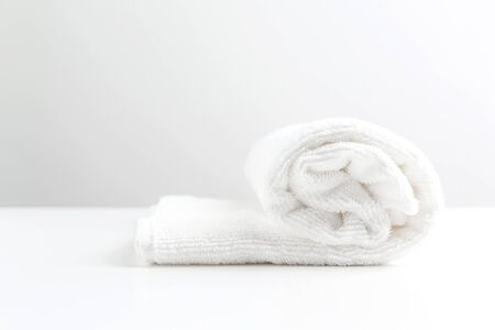 A white towel on a white table. Space for text. Front view. Monochrome color.