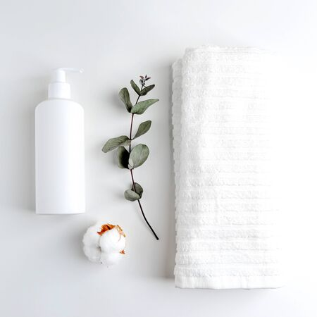 A white towel and a bottle of self-care products on a white table. Front view. Monochrome white color. The minimalist design. Zdjęcie Seryjne