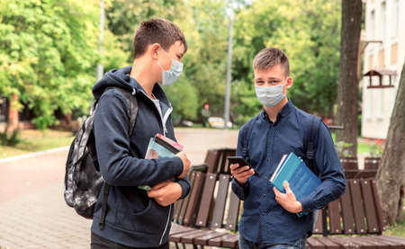Two school friends teen boys are in the schoolyard wearing medical masks on their faces. Stock Photo