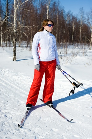 Girl on skis in the winter forest