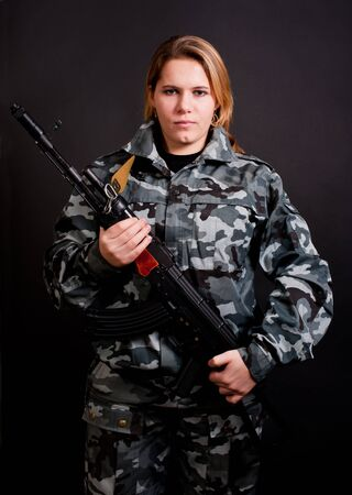 girl in camouflage clothing holding gun Stock Photo