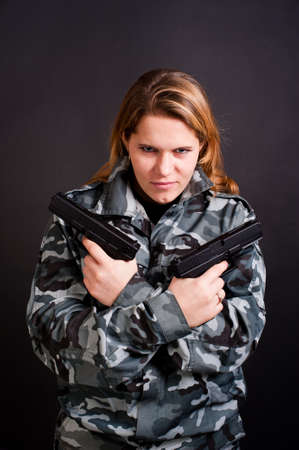 girl in a camouflage clothing holding guns