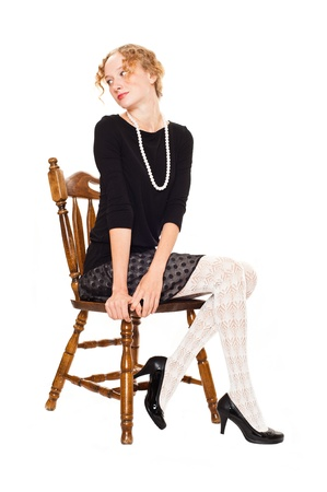 pretty girl sitting on a chair Stock Photo