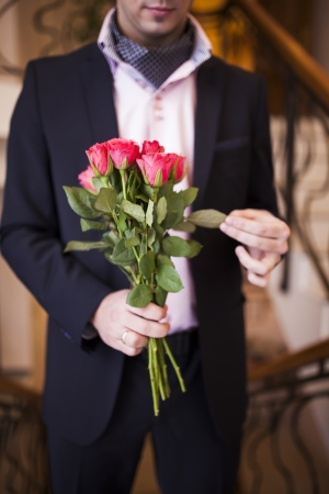 young man in a suit with roses in their hands photo