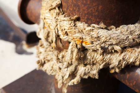cleat: Close-up of a mooring rope with a knotted end tied around a cleat