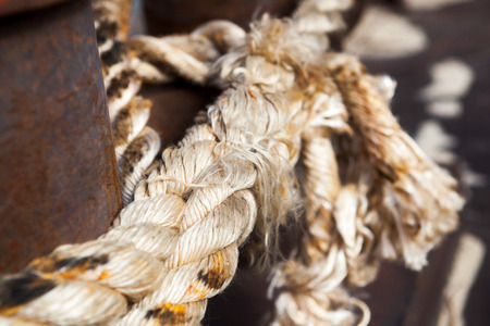 Close-up of a mooring rope with a knotted end tied around a cleat