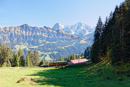 Panoramatic view of Eiger, Jungfraujoch and Jungfrau Region with incoming train from Gruetschalp (Grütschalp) near Grütschalp, Jungfrau Region, Switzerland