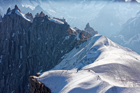 Chamonix, south-east France, Auvergne-Rhône-Alpes. Climbers heading for Mont Blanc. Descending from Aiguille du Midi cable car station towards sunny snow planes and glaciers on border of France and Italy