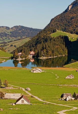 Sunny views of pastures, Seealpsee Inn, Forelle Inn from Oberstofel by Seealpsee lake in Alpstein, Appenzell Alps, Switzerland Stock fotó