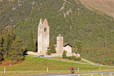 Cyclist passing by San Gian church with its ruined bell tower near Celerina/St. Moritz, Switzerland