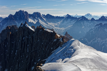 Chamonix, south-east France, Auvergne-Rhône-Alpes. Climbers heading for Mont Blanc. Descending from Aiguille du Midi cable car station towards sunny snow planes and glaciers on border of France and Italy Фото со стока