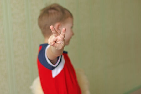 two fingers: the boy shows two fingers. Blurred background. Green background