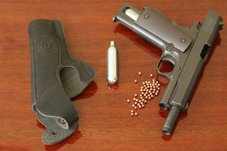 holster: pneumatic gun. cans with gas. the holster. on the wooden background