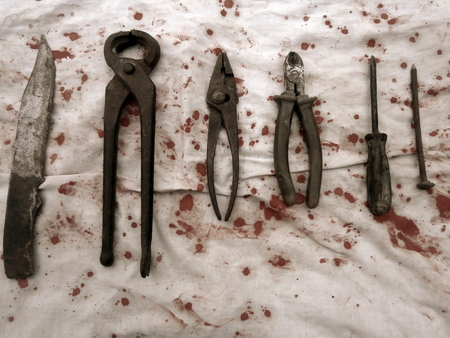 Old rusty tools on a white cloth stained with blood