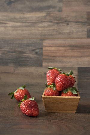willow fruit basket: Fresh strawberries in a bamboo bowl on a wooden background