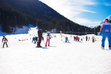 ski walking: Bansko, Bulgaria  January 27, 2016: Ski resort Bansko, Bulgaria, ski slopes and mountain with pine trees, people walking and skiing.