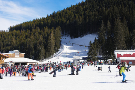 station ski: Bansko, Bulgaria, January 27, 2016:  Bansko ski station, cable car lift and people waiting in line near it in Bansko, Bulgaria. Snow mountain peaks and blue sky at the background Editorial